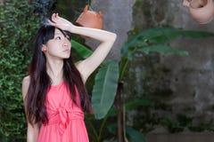 Asiatisk flicka vid växter Arkivfoton
