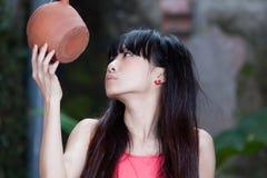 Asiatisk flicka vid växter Arkivbilder