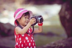 Asiatisk flickafotograf med den yrkesmässiga digitala kameran i friare Arkivfoto