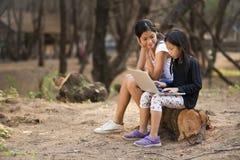 Asiatisk flickastudie för två barn i utomhus- Arkivfoto