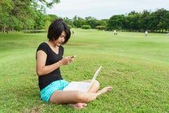 Asiatisk flickatyp någon text på hennes mobiltelefon Arkivfoto