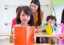 Asiatisk flickaungeläsebok i klassrum och, medan läraren undervisar royaltyfria foton