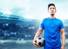 Asiatisk fotbollsspelareman i den blåa ärmlös tröja som rymmer bollen på fotbollfältet arkivfoton