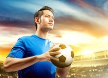 Asiatisk fotbollsspelareman i den bl?a ?rml?s tr?ja som rymmer bollen p? fotbollf?ltet royaltyfri fotografi