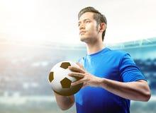 Asiatisk fotbollsspelareman i den bl?a ?rml?s tr?ja som rymmer bollen p? fotbollf?ltet arkivfoton