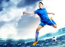 Asiatisk fotbollsspelareman som hoppar och sparkar bollen i luften royaltyfri fotografi