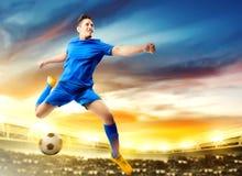 Asiatisk fotbollsspelareman som hoppar och sparkar bollen i luften fotografering för bildbyråer