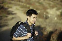 Asiatisk fotvandrare som upp går kulle Royaltyfria Bilder