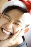 Asiatisk framsida för ljust leende med den santa hatten Royaltyfri Foto