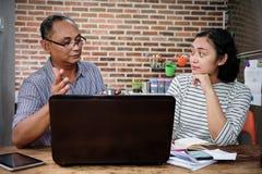 Asiatisk frilans- affärsman som ger presentation till det kvinnligClientat hemmet royaltyfria bilder