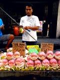 Asiatisk gatuförsäljare som säljer pomelofrukt i en marknad i quiapoen, manila, philippines i asia royaltyfri bild