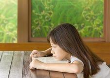 Asiatisk gir som tröttas på skrivbordet, medan lära Arkivfoto