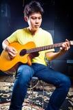 Asiatisk gitarrist som spelar musik i inspelningstudio arkivbild