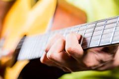 Asiatisk gitarrist som spelar musik i inspelningstudio Arkivfoto
