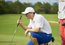 Asiatisk golfare som huka sig ned i golfbanan som siktar och förbereder sig för att sätta Royaltyfri Foto