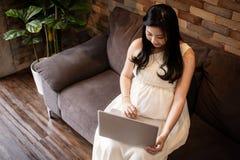 Asiatisk gravid kvinna som hemma använder datorbärbara datorn royaltyfri bild