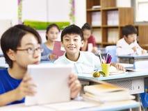 Asiatisk grundskola för barn mellan 5 och 11 årstudent som använder minnestavlan i klassrum Arkivfoton
