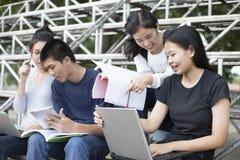 Asiatisk grupp av studenter som använder minnestavlan och anteckningsboken som delar med t royaltyfria bilder