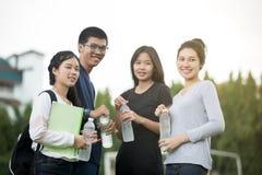 Asiatisk grupp av studenter som delar med idéerna för att arbeta och Arkivbilder