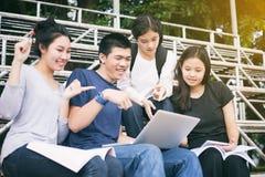 Asiatisk grupp av studenter som delar med idéerna för att arbeta på th Arkivbild