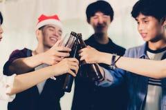 Asiatisk grupp av vänner som har partiet med alkoholiserade öldrinkar och ungdomarsom tycker om på en stång som rostar coctailar  arkivbilder