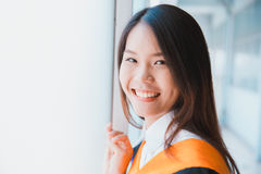 Asiatisk gullig kvinnaleendeavläggande av examen arkivbild