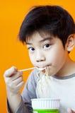 Asiatisk gullig pojke med nudelkoppen Arkivbilder