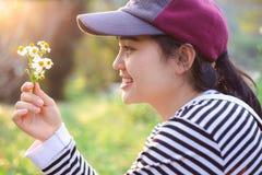 Asiatisk gullig ung tonårig flicka som ler och ser gräsblomman royaltyfri bild