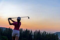 Asiatisk gunga för slaget för kvinnagolfspelaren sköt golfboll på den gröna solnedgången av den gröna klubban i aftontid Royaltyfri Bild