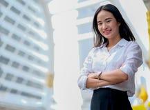 Asiatisk härlig affärsflicka med den vita skjortahandlingen som säker och ställning bland hög byggnad i storstaden i dagtid arkivfoton