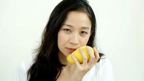 Asiatisk härlig kvinna som äter att posera med mango Sommarfröjd t Fotografering för Bildbyråer