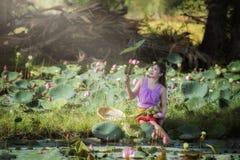Asiatisk härlig kvinna som går i lotusblommafält arkivfoto