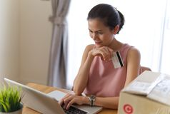 Asiatisk härlig le flicka som direktanslutet köper från internet genom att använda kreditkorten för betalning arkivfoto