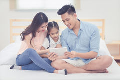 Asiatisk hållande ögonen på tecknad film för fader och för moder med dottern Royaltyfri Foto