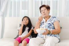 Asiatisk hög kvinna som äter popcorn med hennes barnbarn Fotografering för Bildbyråer