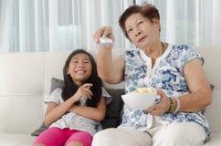 Asiatisk hög kvinna som äter popcorn med hennes barnbarn Royaltyfri Fotografi