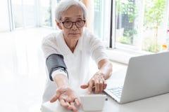 Asiatisk hög kvinna som hemma kontrollerar blodtryck, vård- kontroll för äldre folk genom att använda en blodtryckbildskärm som k arkivfoto