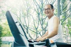 Asiatisk hög man som skjuter knappen och springen på en trampkvarn Royaltyfri Bild