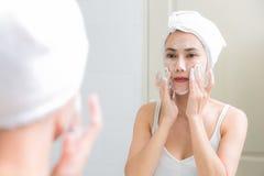 Asiatisk hud för kvinnalokalvårdframsidan tycker sig om med bubblacleansi Arkivbilder