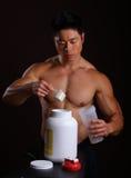 Asiatisk huvuddelbyggmästare som häller en skopa av proteinmixen Arkivbild