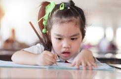 Asiatisk (Japan, kines, Korea) nätt flickahåll för utbildning och för skolabegrepp en bok och en läsning royaltyfria bilder