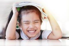 Asiatisk (Japan, kines, Korea) nätt flickahåll för utbildning och för skolabegrepp en bok och en läsning arkivfoto