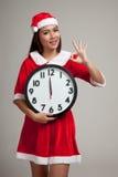 Asiatisk julflicka i den Santa Claus kläder och klockan på midnigh Fotografering för Bildbyråer