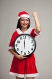 Asiatisk julflicka i den Santa Claus kläder och klockan på midnigh Royaltyfri Foto