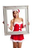 Asiatisk julflicka med den Santa Claus kläder och ramen Royaltyfri Foto