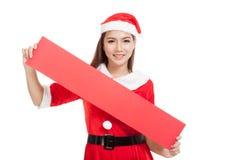 Asiatisk julflicka med Santa Claus kläder med det tomma tecknet Fotografering för Bildbyråer