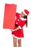 Asiatisk julflicka med Santa Claus kläder med det tomma tecknet Royaltyfria Foton