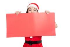 Asiatisk julflicka med Santa Claus kläder med det tomma tecknet Arkivbilder