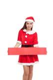 Asiatisk julflicka med Santa Claus kläder med det tomma tecknet Arkivbild