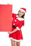 Asiatisk julflicka med Santa Claus kläder med det tomma tecknet Royaltyfria Bilder
